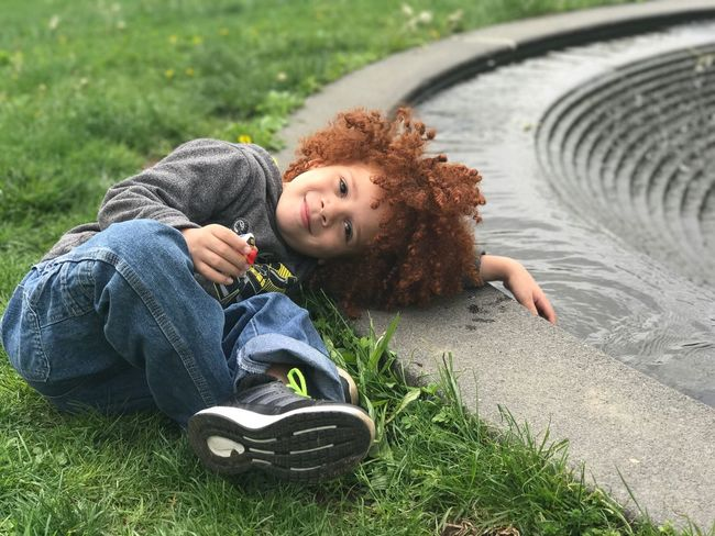 Child laying in the grass. Childhood Child Beautiful Child Redhair Redhead Water Outdoors Joy Curly Hair Happy Portrait Lying Down Casual Clothing Smiling Grass One Person Looking At Camera Happiness Leisure Activity Day Redhead Full Length Relaxation Cheerful Done That. Summer Exploratorium