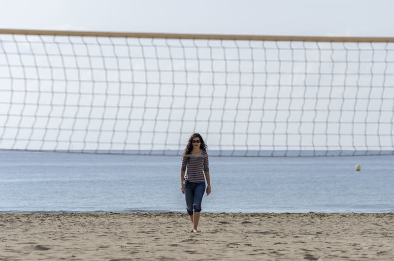 Woman walking at beach seen through volleyball net against sky