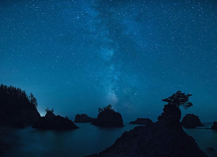 Scenic View Of Rock Formations In Sea Against Star Field Sky At Night