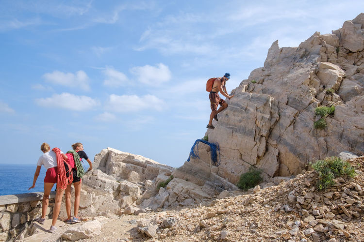 People climbing on rock against sky