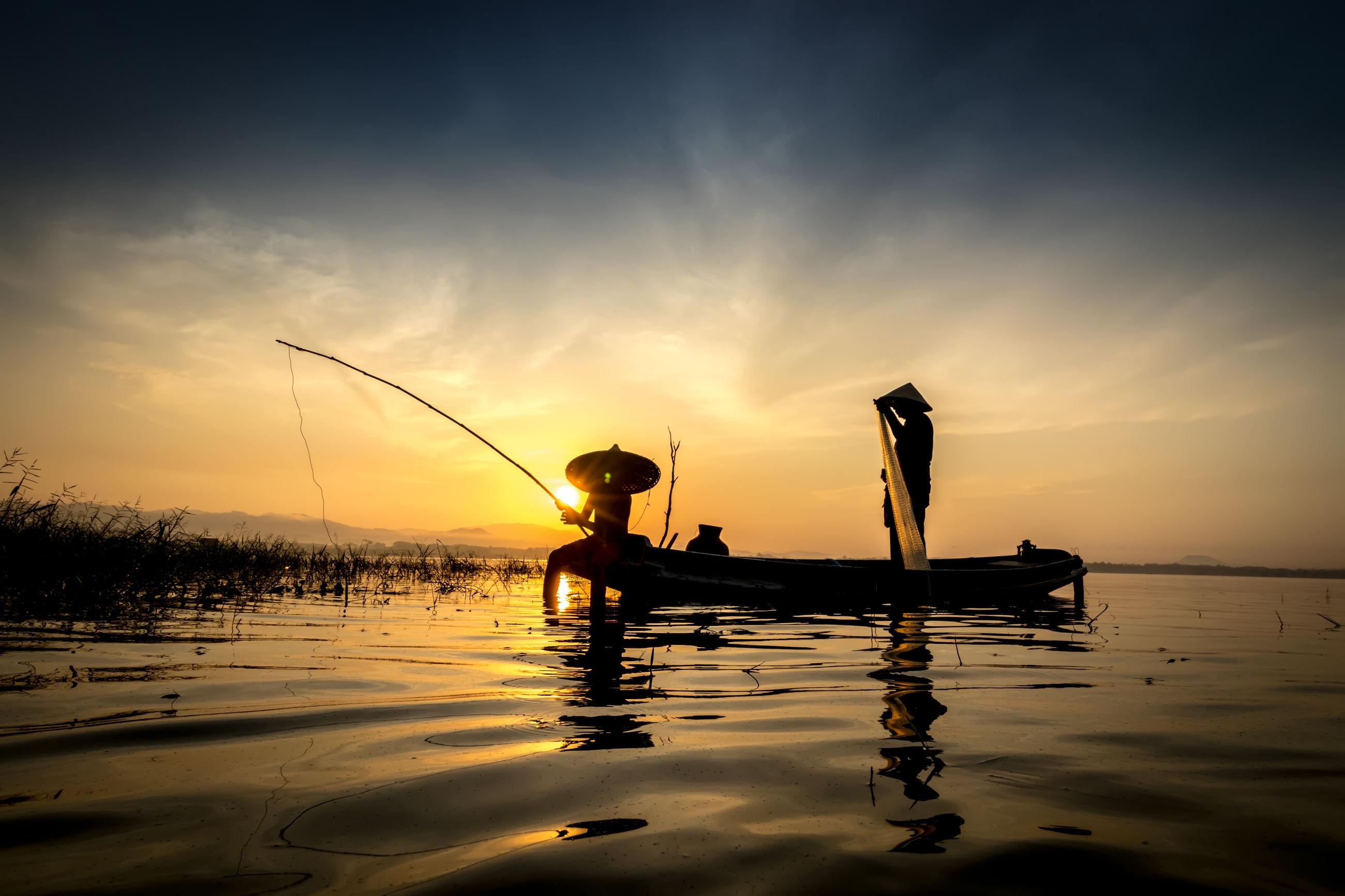 SILHOUETTE MEN FISHING IN BOAT AGAINST SKY AT SUNSET