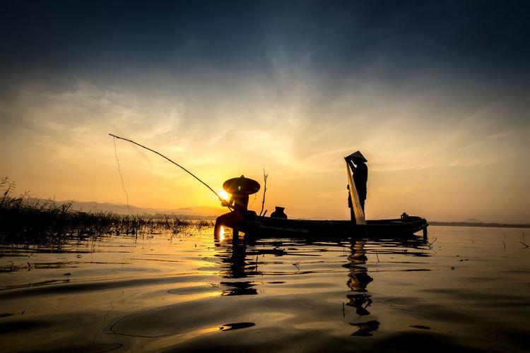 Silhouette men fishing in boat against sky during sunset