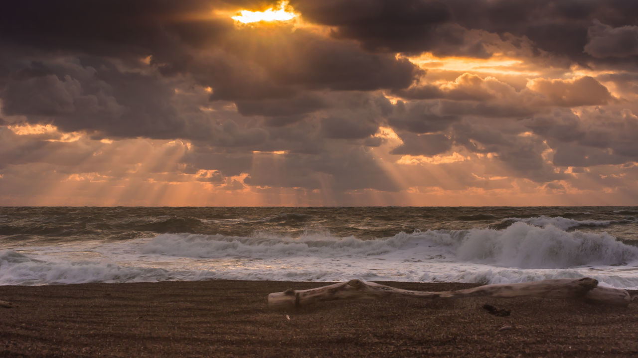Sunlight Piercing Through Clouds Onto Sand Beach