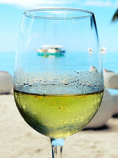 Close-up of wine in glass at beach