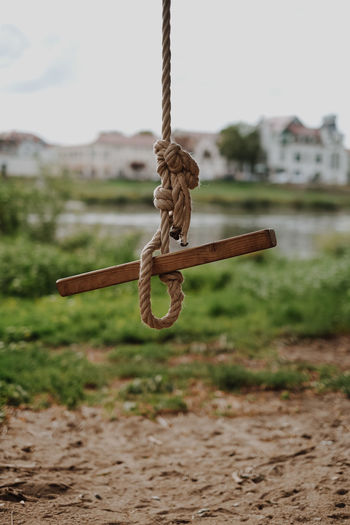 Close-up of rope tied on metal chain swing