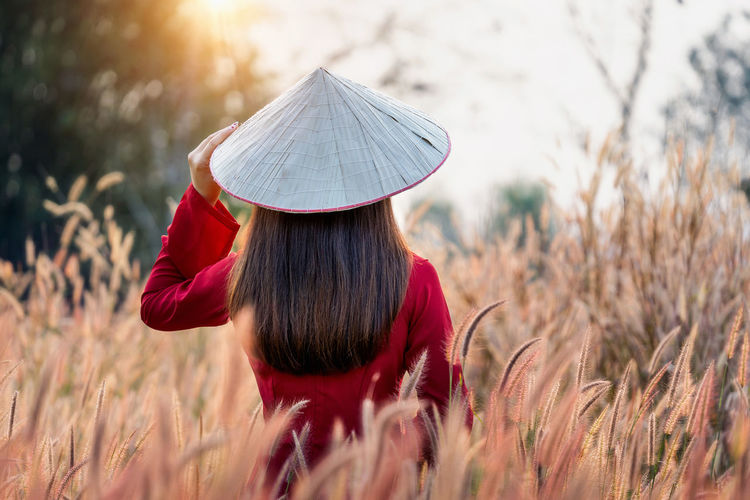 Asian woman wearing Vietnam culture traditional in african fountain flower field. One Person Land Field Plant Women Adult Rear View Hat Nature Real People Sunlight Selective Focus Day Lifestyles Growth Leisure Activity Landscape Rural Scene Casual Clothing Hairstyle Outdoors Hair