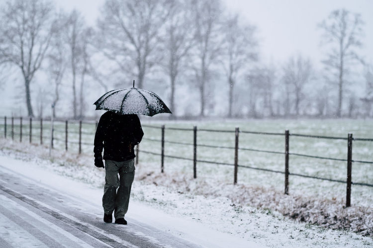 Rear view of person walking on snow covered landscape during rainy season