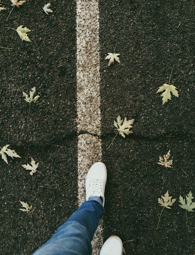 Low section of woman walking on road by fallen maple leaves during autumn