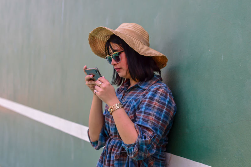Woman wearing sunglasses and hat while using mobile phone against wall