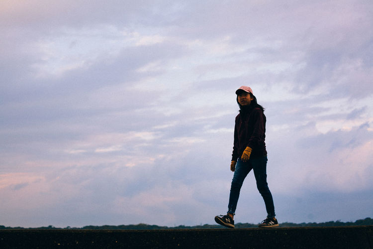 Full length of young woman standing against sky