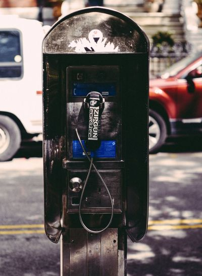 Black pay phone in city