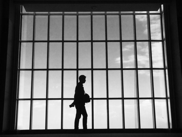 Silhouette man walking by glass window