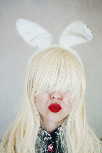 Close-Up Of Woman Wearing Rabbit Ears Headband Against Wall