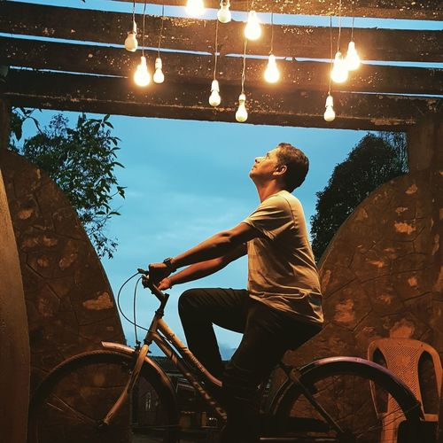 Side view of mature man looking at illuminated light bulbs while riding bicycle at sunset