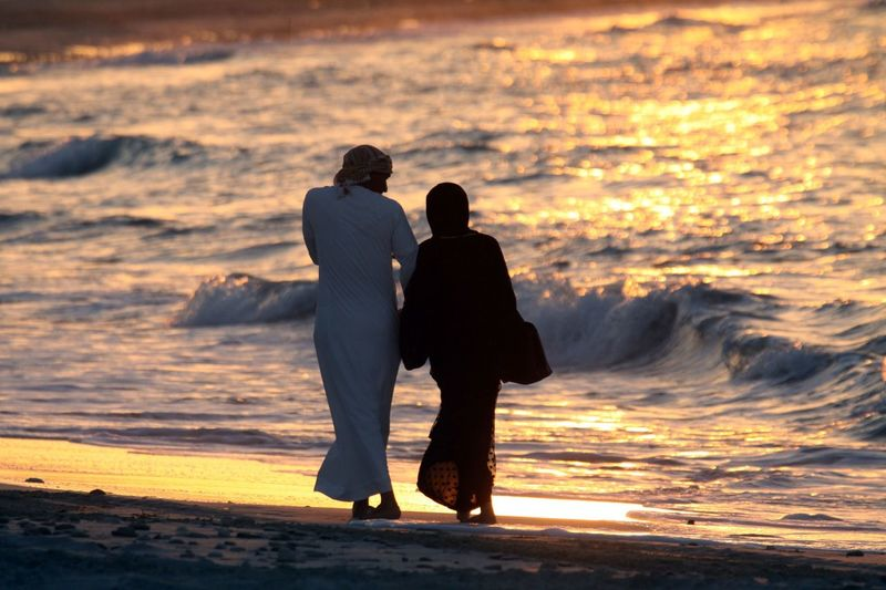 Arabian Beach Beauty In Nature Bonding Couple - Relationship Full Length Horizon Over Water Leisure Activity Lifestyles Love Men Nature Outdoors Real People Rear View Romance Scenics Sea Silhouette Sunset Togetherness Two People Vacations Walking Water Women
