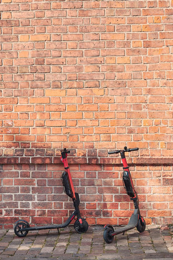 Push scooters against brick wall