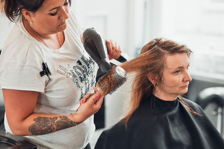 Hairdresser drying woman hair in salon