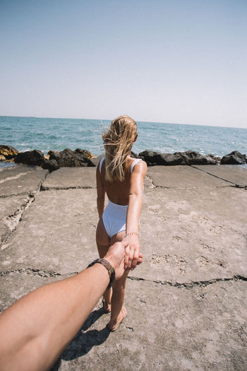 Cropped image of man holding woman hand at beach during sunny day
