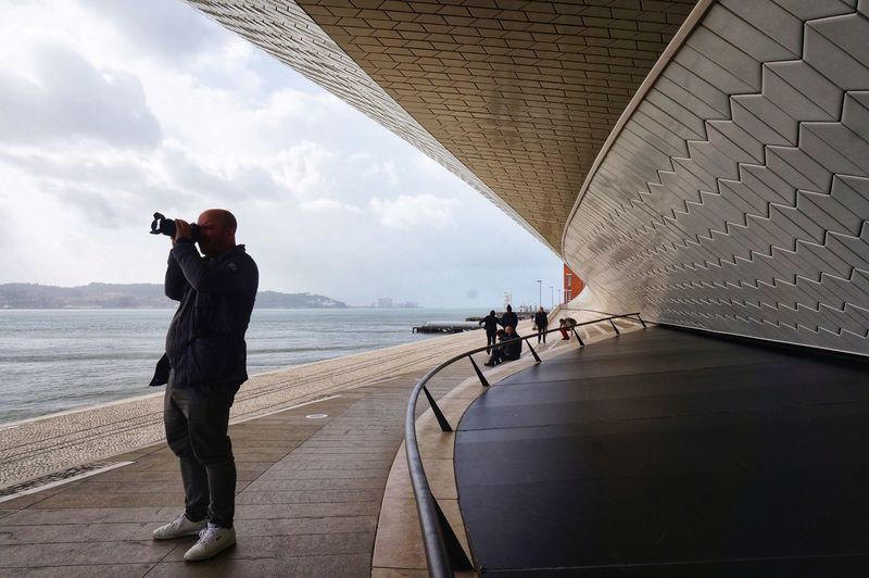 People photographing by sea against sky