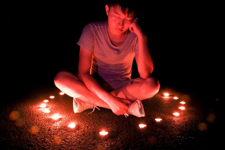 Man With Closed Eyes Sitting Amidst Lit Diya In Darkroom