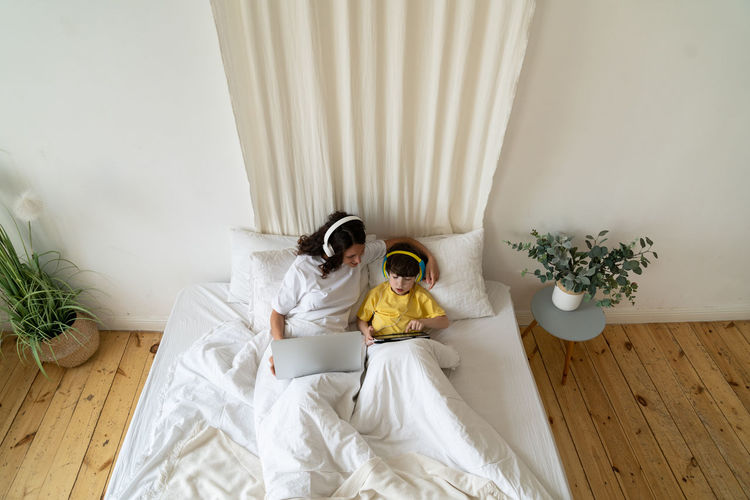 High angle view of woman sitting on bed at home