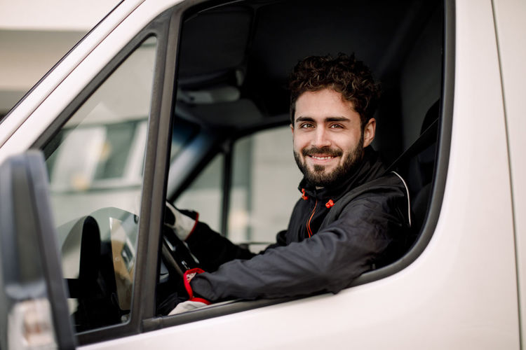 Portrait of a smiling young man in car