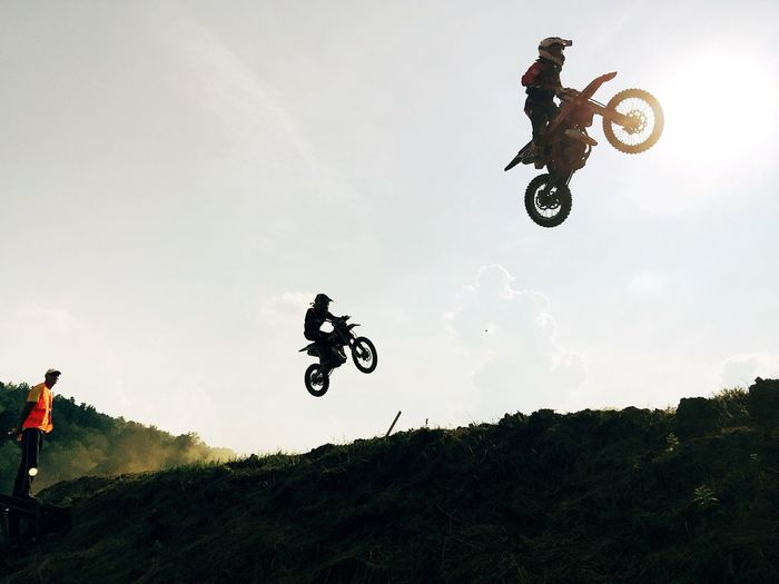 Low angle view of silhouette bikers with motorcycles jumping against sky