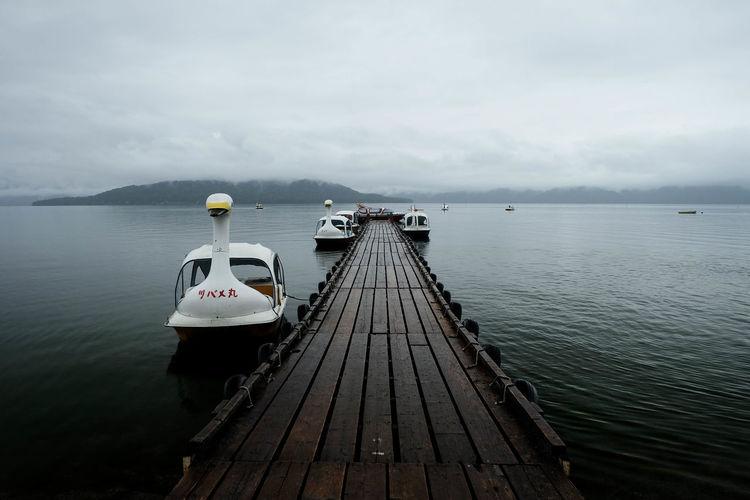 Motorboats moored at pier on caldera lake at akan national park