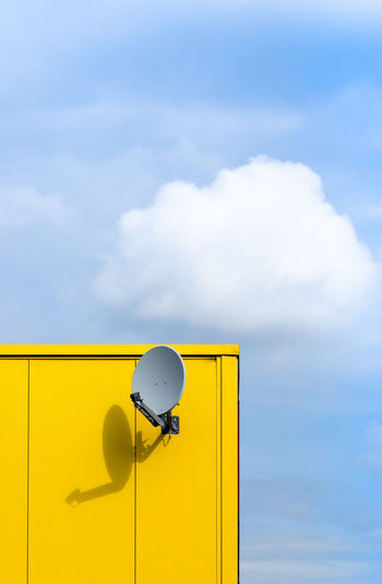 Low angle view of yellow telephone against sky