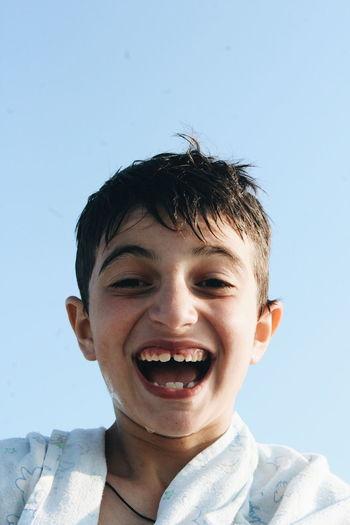 Portrait of smiling boy against sky