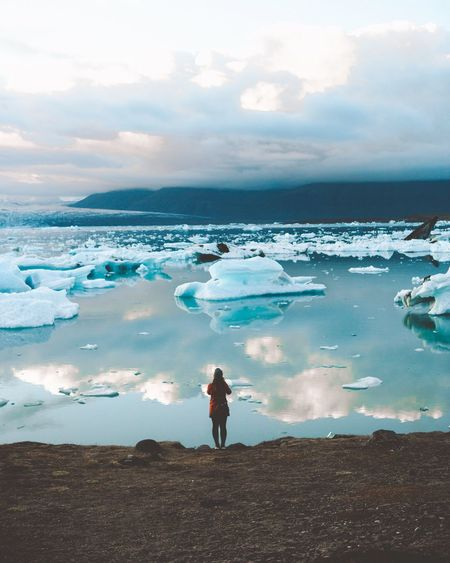 Rear View Of Woman Standing Against Ice Bergs