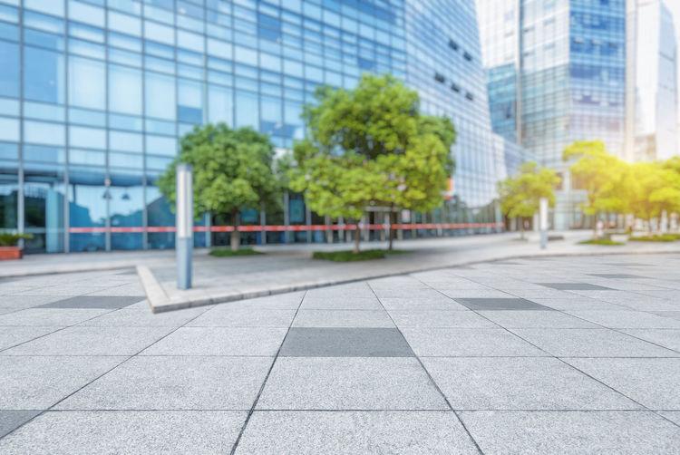 Empty footpath by modern buildings in city
