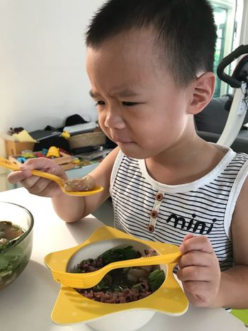 Childhood Child Males  Real People Boys Lifestyles One Person Holding Casual Clothing Eating Food Table Front View Sitting Men Indoors  Food And Drink Innocence
