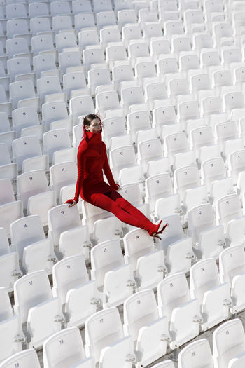 Full length of fashion model in red sitting on white chairs at stadium