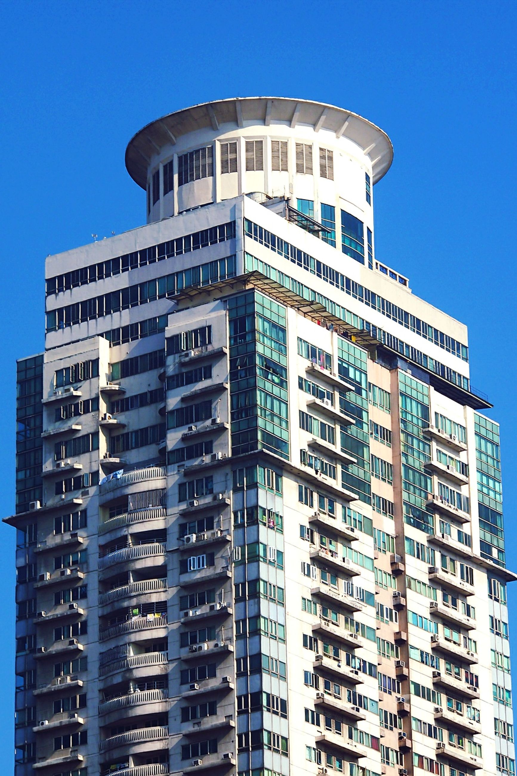 building exterior, architecture, built structure, low angle view, clear sky, blue, window, building, city, residential building, modern, residential structure, office building, day, sunlight, outdoors, apartment, tall - high, no people, balcony