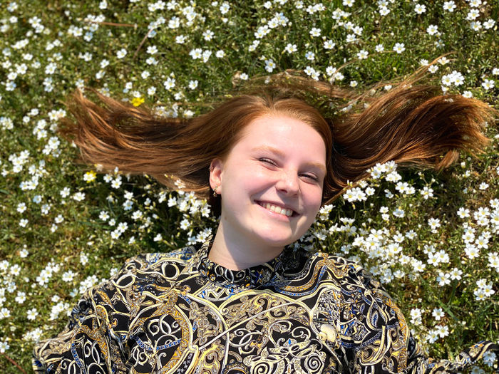 High angle view of smiling woman lying over flowers on field