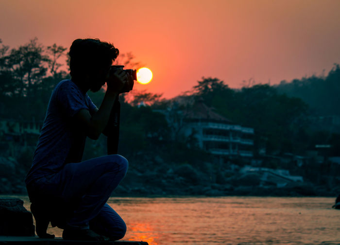 Side view of man photographing with camera by lake against orange sky