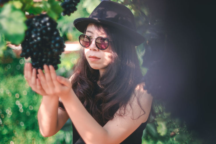 Portrait of young woman wearing sunglasses against plants