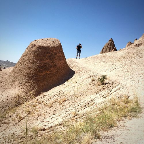 Low angle view of man at cappadocia against clear blue sky on sunny day