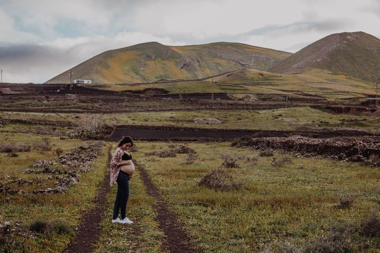 Full length of pregnant woman standing on field against sky