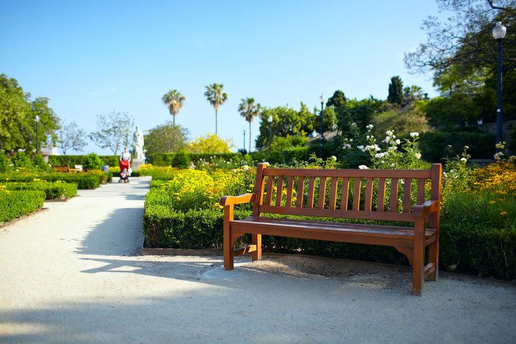 Empty wooden bench against clear sky in garden