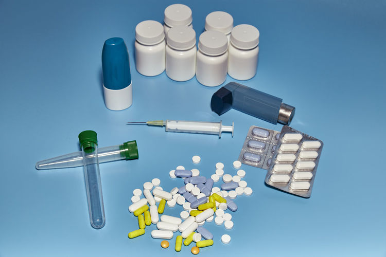 Group of medications varied on a blue background of a pharmacy or a hospital