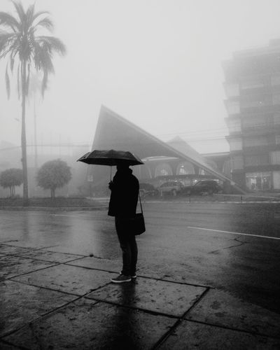 Full Length Of Man With Umbrella On Street Against Sky During Rainy Season
