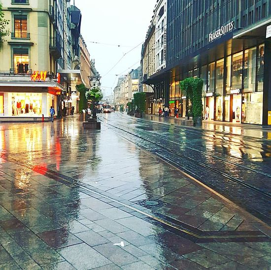 The Street Photographer - 2017 EyeEm Awards Wet Rain Water Rainy Season Reflection City Outdoors Torrential Rain Building Exterior Day Architecture No People Sky Walking Swiss Switzerland Geneva Luxury Lux Brand Weather Rain Rainy Days Cloud Done That.