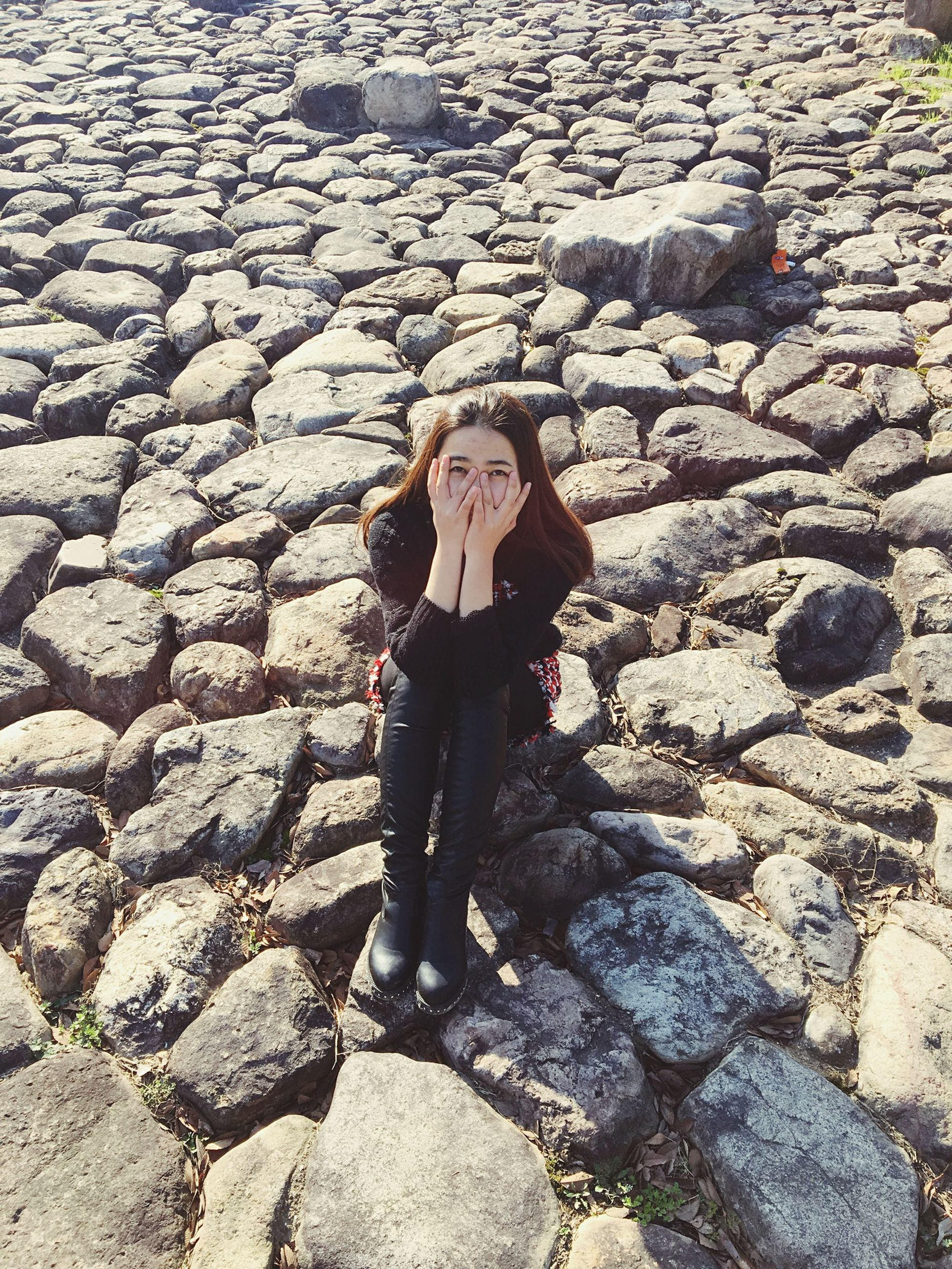 lifestyles, standing, leisure activity, full length, high angle view, casual clothing, portrait, person, front view, day, outdoors, street, looking at camera, childhood, young adult, cobblestone, young women, stone wall