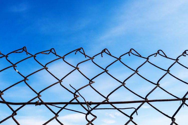 Metal grille fence against the sky