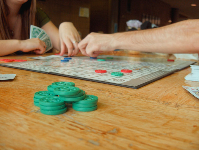 Arm Board Games Close-up Communication Day Fun Gambling Chip Game Pieces Hands Human Hand Indoors  Leisure Activity Leisure Games Low Tech People Playing Playing Cards Real People Relaxation Sitting Table Young Adult