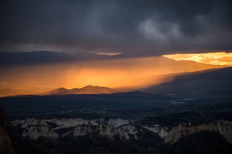 Scenic view of mountains against dramatic sky at sunset
