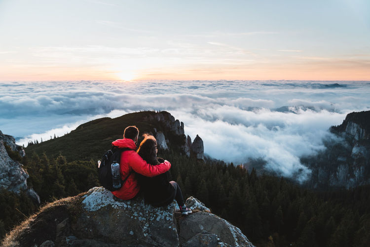 People sitting on rock looking at mountains against sky during sunset