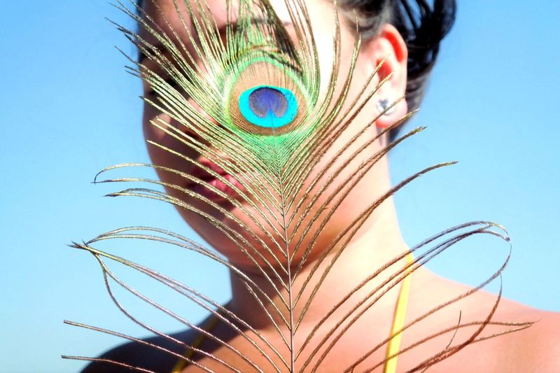 Close-up of young woman with peacock feather